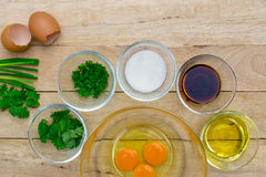 Raw eggs and ingredients on  wooden background. Stock Photo