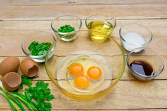 Raw eggs and ingredients on  wooden background. Stock Image