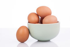 Raw eggs isolated in clay bowl Stock Images
