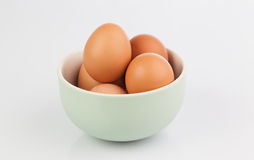 Raw eggs isolated in clay bowl Stock Image