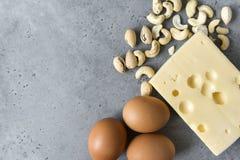 3 raw eggs, Maasdam cheese, cashew nuts on grey concrete background. 3 raw eggs, cashew nuts, Maasdam cheese,  on grey concrete background stock photos