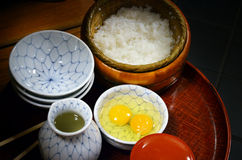 Raw eggs and rice. Ingredients to prepare Tamago Kake Gohan, simple Japanese meal for breakfast, made by serving raw egg over hot steamed Japanese rice Stock Image