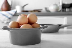 Raw eggs in saucepan. On kitchen table Royalty Free Stock Images