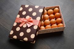 Raw eggs in a semi open gift box on black background royalty free stock photo