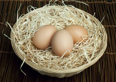 Raw eggs in a wicker basket Royalty Free Stock Image