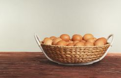 Raw eggs in wicker basket on table. Raw eggs in wicker basket on wooden table Stock Photography