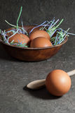 Raw eggs in wooden bowl on gray background Stock Images