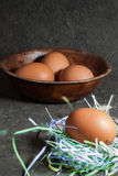 Raw eggs in wooden bowl on gray background Royalty Free Stock Photos