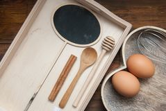 Raw Eggs with wooden spooon and Baking tools. Bake or food Background. Dark rustic Wooden Background and Heart Shape Box, with cop Stock Images