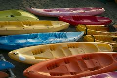 Raw of empty Colorful kayaks aligned on the beach at sunset. Royalty Free Stock Photo