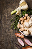 Raw eryngii Mushrooms in a metal bowl with garlic, thyme and chives Stock Image