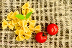 Raw farfalle. Close up of  row farfalle pasta .with cherry tomatoes and fresh basil .Italian healthy food background. View from above Stock Image