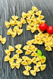 Raw farfalle. Close up of  row farfalle pasta on   marble slate .wirh cherry tomatoes and fresh basil .Italian healthy food background. View from above Royalty Free Stock Image