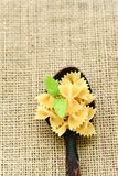 Raw farfalle. Close up of  row farfalle pasta on  black slate .wirh cherry tomatoes and fresh basil .Italian healthy food background. View from above Royalty Free Stock Photos