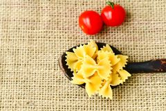 Raw farfalle. Close up of  row farfalle pasta on  black slate .wirh cherry tomatoes and fresh basil .Italian healthy food background. View from above Royalty Free Stock Images