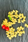 Raw farfalle. Close up of  row farfalle pasta on  black slate .wirh cherry tomatoes and fresh basil .Italian healthy food background. View from above Stock Photography