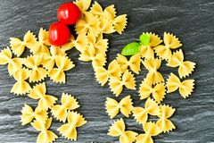 Raw  farfalle. Close up of  row farfalle pasta on   marble slate .wirh cherry tomatoes and fresh basil .Italian healthy food background. View from above Royalty Free Stock Photography