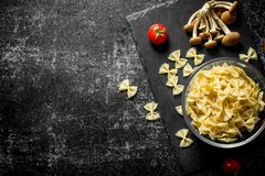 Raw Farfalle pasta in a bowl with mushrooms and tomatoes. On black rustic background stock photography