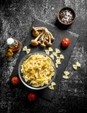 Raw Farfalle pasta in a bowl with mushrooms and tomatoes. On black rustic background stock images