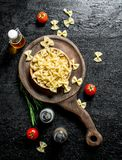 Raw Farfalle pasta in a bowl with the rosemary, tomatoes, spices and oil. On black rustic background royalty free stock photo
