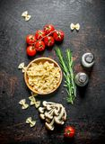 Raw Farfalle pasta in a bowl with the tomatoes, rosemary, mushrooms and spices. On rustic background royalty free stock images