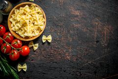 Raw Farfalle pasta in a bowl with the tomatoes, rosemary, mushrooms and spices. On rustic background royalty free stock image