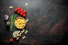 Raw Farfalle pasta in a bowl with the tomatoes, rosemary, mushrooms and spices. On rustic background royalty free stock photo