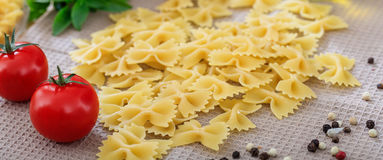 Raw farfalle pasta with tomatoes. And basil Stock Photos