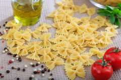 Raw farfalle pasta with tomatoes. And basil Stock Photo