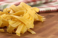 Raw fettuccine. Beautiful fresh and raw fettuccine on fine wood kitchen station shallow DOF royalty free stock image