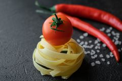Raw fettuccine pasta with fresh tomato, coarse sea salt and chili peppers stock photos
