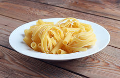 Raw fettucini on a white plate Royalty Free Stock Photos