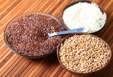 Raw fibre. Bowls of rice, wheat and flax seeds over wooden background Stock Photo