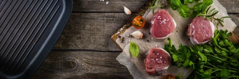 Raw filet mignon meat cuts with spice and herbs. Wood background Stock Photography