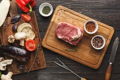 Raw filet mignon steak on wooden board. Raw filet mignon steak. Fresh beef meat on wooden board with vegetables, fork and knife. Organic ingredients for stock images