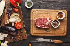 Raw filet mignon steak on wooden board. Raw filet mignon steak. Fresh beef meat on wooden board with vegetables and knife. Organic ingredients for restaurant royalty free stock images