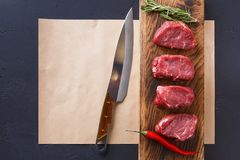 Raw beef filet mignon steaks on wooden board and craft papper. Raw filet mignon steaks. Fresh beef meat, rosemary and chilli on wooden board on craft paper at Royalty Free Stock Photography