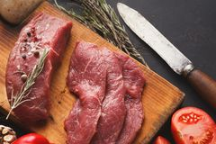 Raw beef filet mignon steaks on wooden board. Raw filet mignon steaks. Fresh beef meat, rosemary on wooden board at black background. Organic ingredients for royalty free stock images