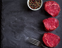 Raw filet mignon steaks. Raw fresh marbled filet mignon steaks and fork, ready for roasting on black concrete background. Raw juicy filet mignon steaks. Space Royalty Free Stock Photos