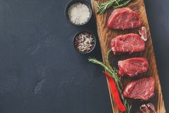 Filet mignon steaks and spices on wood at black background. Raw filet mignon steaks with herbs and spices. Cooking ingredients for restaurant dish. Fresh meat Stock Photo