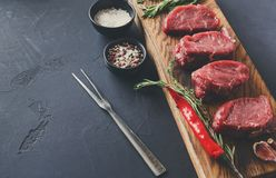 Filet mignon steaks and spices on wood at black background. Raw filet mignon steaks with herbs and spices. Cooking ingredients for restaurant dish. Fresh meat Stock Images