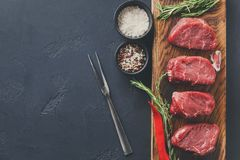 Filet mignon steaks and spices on wood at black background. Raw filet mignon steaks with herbs and spices. Ingredients for restaurant dish. Fresh meat, salt Royalty Free Stock Photography