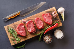 Filet mignon steaks and spices on wood at black background. Raw filet mignon steaks with herbs and spices. Modern restaurant cuisine still life with organic beef royalty free stock photos