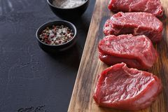 Raw beef filet mignon steaks with spices on wooden board at blac. Raw filet mignon steaks with spices closeup. Slices of fresh beef meat arranged in a row on stock image