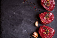 Raw filet mignon steaks with spices. Raw fresh marbled filet mignon steaks with spices ready for roasting on black concrete background. Filet mignon steaks royalty free stock images