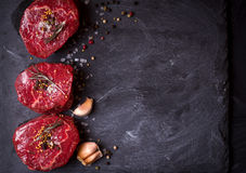 Raw filet mignon steaks with spices. Raw fresh marbled filet mignon steaks with seasonings ready for roasting on black concrete background. Filet mignon steaks royalty free stock image