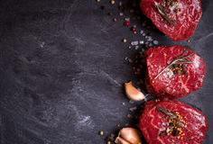 Raw filet mignon steaks with spices. Raw fresh marbled filet mignon steaks with seasonings ready for roasting on black concrete background. Filet mignon steaks stock photography