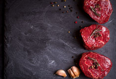 Raw filet mignon steaks with spices. Raw fresh marbled filet mignon steaks with seasonings ready for roasting on black concrete background. Filet mignon steaks royalty free stock images