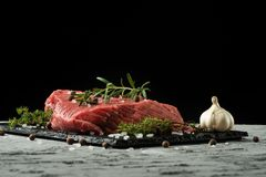 Raw fillet of beef steak with rosemary, thyme, and spices on a blackboard. stock photography