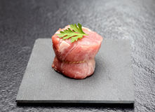 Raw fillet medallions of young pork with parsley on a board of black basalt on a gray background Royalty Free Stock Photography